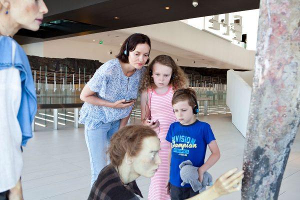 Een jong gezin (moeder met dochter en zoon) volgt samen een audiotour en bekijkt het kunstwerk van twee Romeinse vrouwen in Museum Hoge Woerd aandachtig.