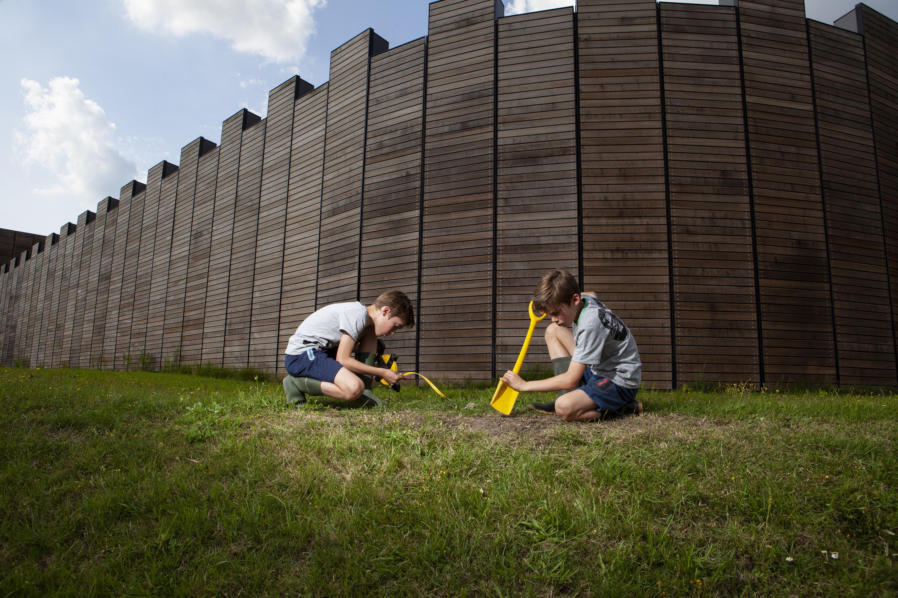 Twee jonge, mannelijke, onderzoekers zijn met een schep en een meetlint in de weer voor de muren van het Castellum.