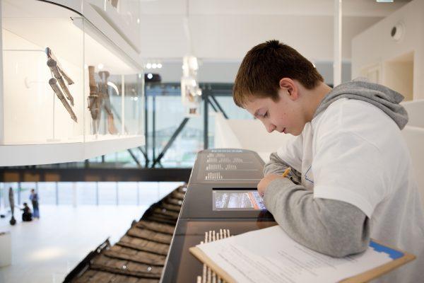 Een jonge jongen, een archeoloog in de dop, bekijkt de interactieve vitrine rondom het romeinse schip.