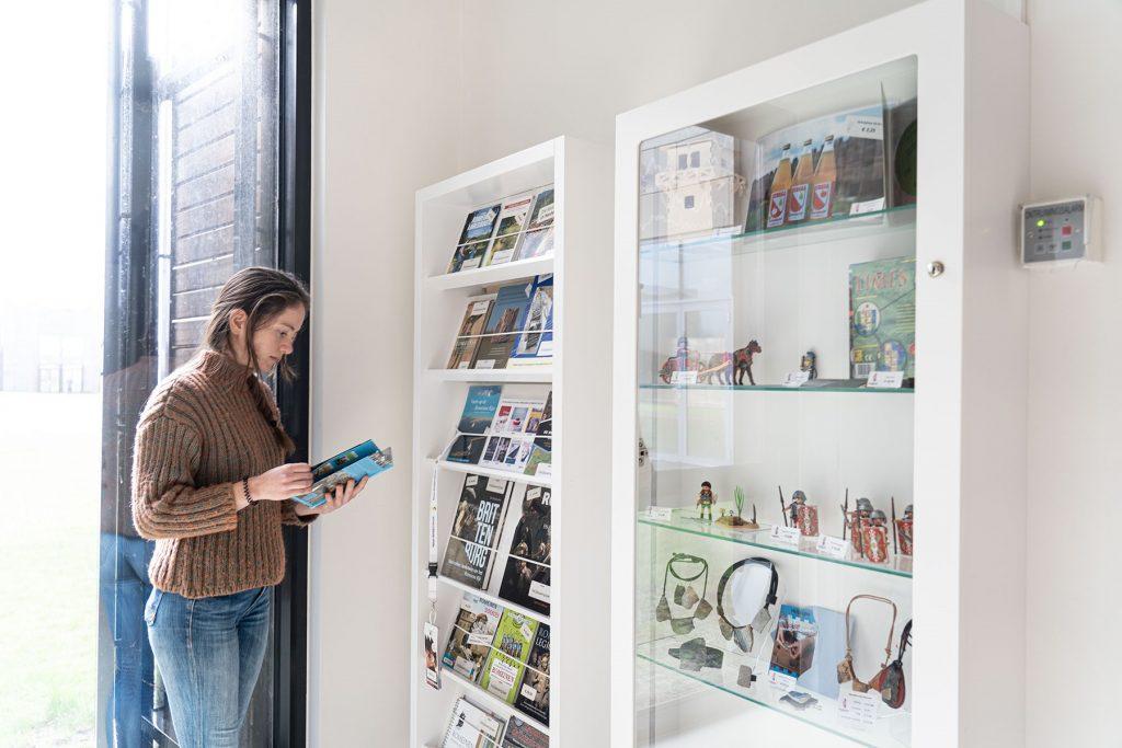 Een vrouw staat naast de glazen vitrines van de museumwinkel en leest een folder.
