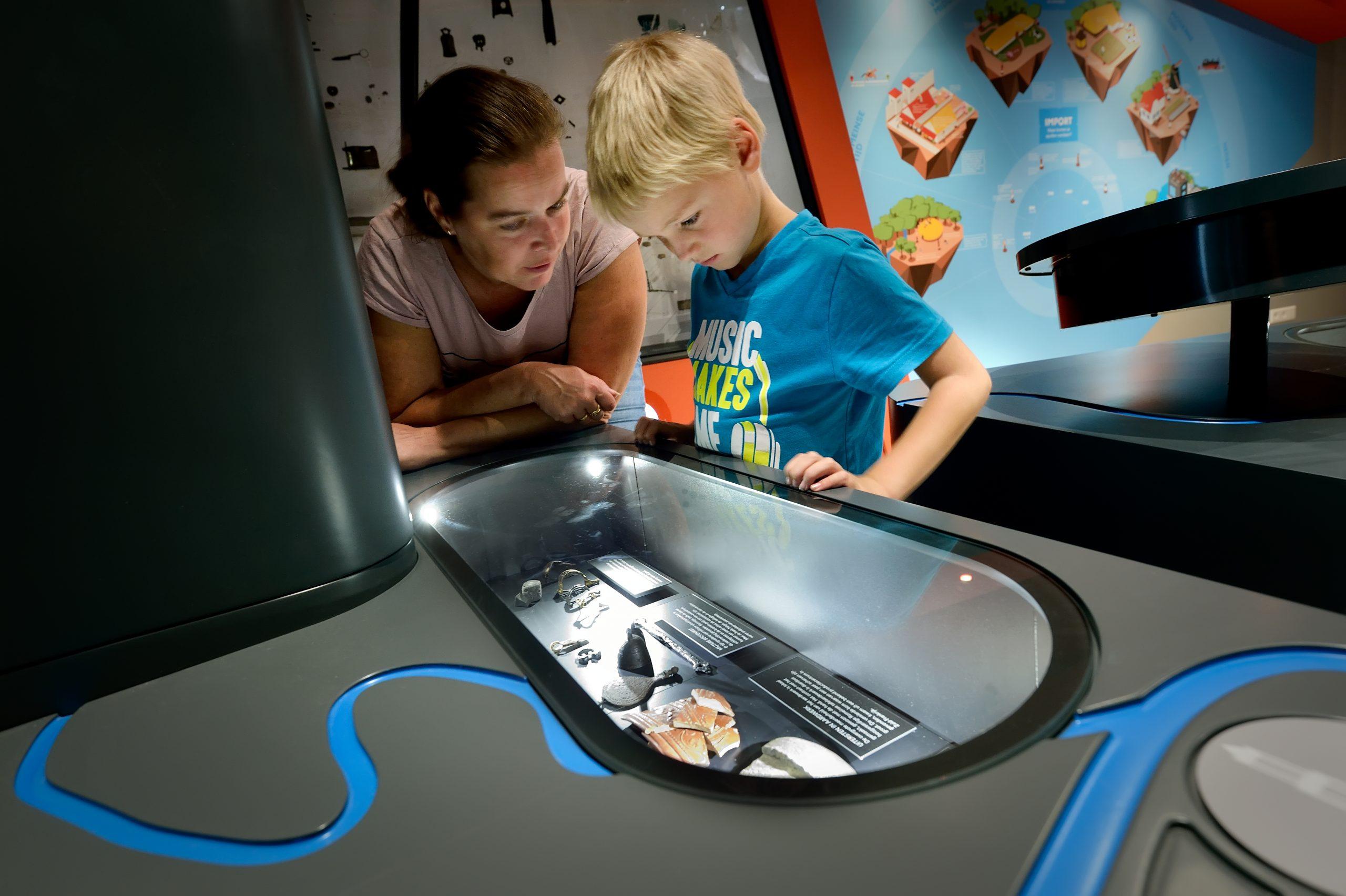 Moeder en kind bekijken een stuk binnen de interactieve expositie bij Museum Hoge Woerd