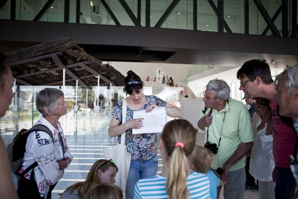Een vrouwelijke gids wijst informatie aan op een hand-out. Een groep geïnteresseerde bezoekers van verschillende leeftijden kijkt en luistert aandachtig naar haar.