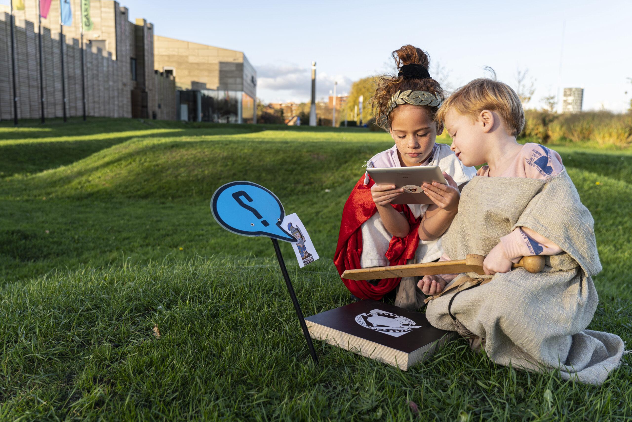 Een jongen en een meisje zijn gekleed in Romeins kostuum en zitten gehurkt voor een Romeins castellum. Ze kijken samen naar een Ipad die het meisje vasthoudt.