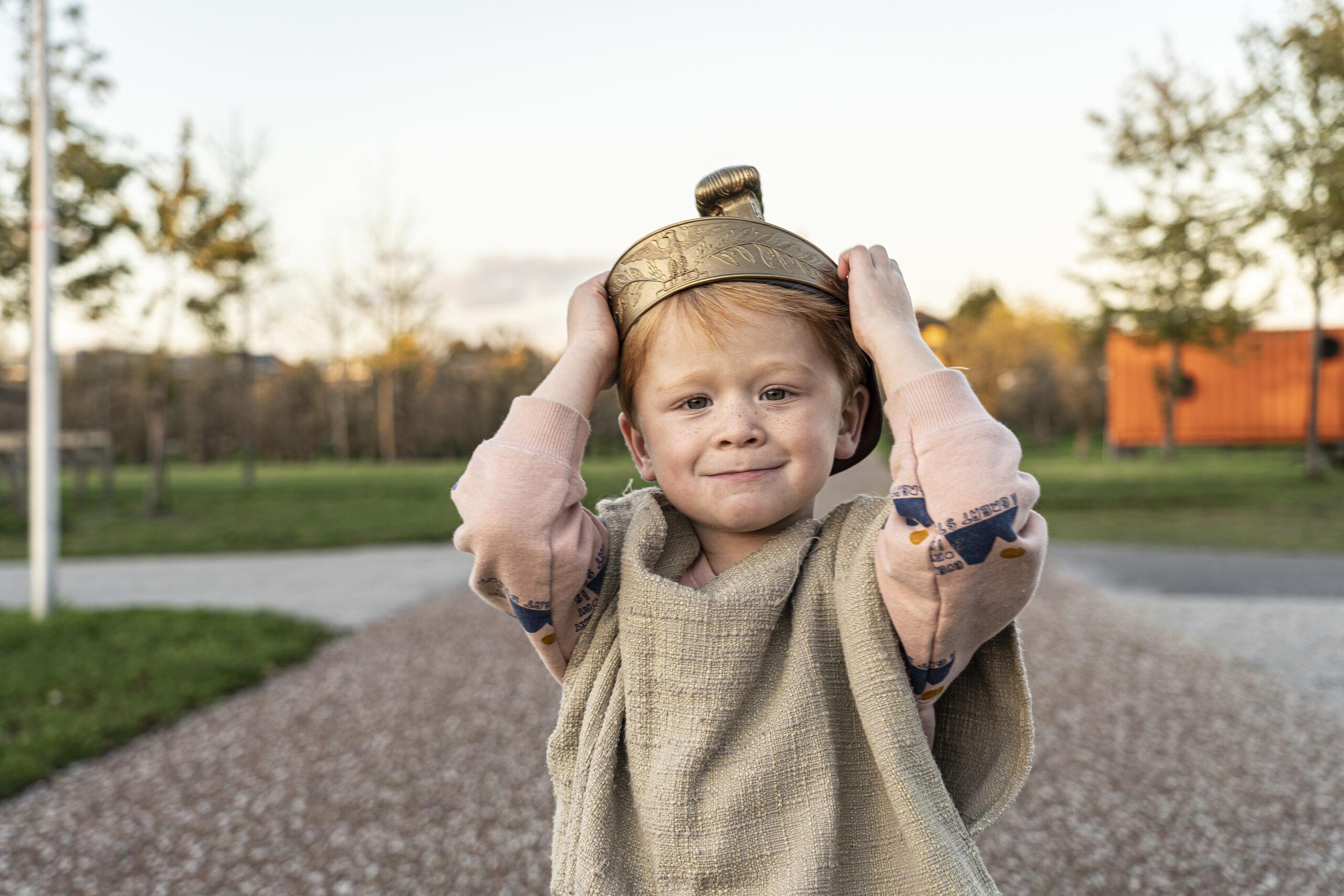 Een jongetje is gekleed in Romeins kostuum en houdt met beide handen zijn Romeinse helm, die hij op zijn hoofd draagt, vast. Het jongetje glimlacht in de camera.
