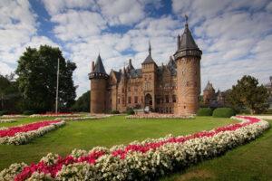 Foto van Kasteel de Haar, met een grasveld met bloemen op de voorgrond en een blauwe lucht met witte wolken boven het kasteel. Bron: https://www.ontdek-utrecht.nl/locatie/kasteel-de-haar