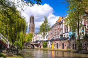 Utrechtse gracht met grachtenpanden aan weerszijden en de Domtoren in de achtergrond.